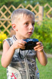 The boy with the camera. The surprised little boy with the camera Royalty Free Stock Photography