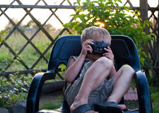 The boy with a camera. The child with camera sits in a black plastic armchair in the warm summer evening Royalty Free Stock Photography