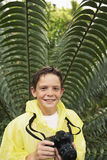 Boy With Camera By Large Fern In Forest Royalty Free Stock Images
