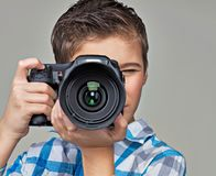 Boy with camera taking pictures. Stock Photos