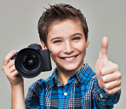Boy with camera taking pictures. Happy fun boy  with dslr camera showing the thumb up Royalty Free Stock Images