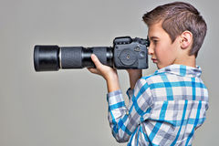 Boy with camera taking pictures. Royalty Free Stock Images
