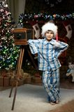 Boy with a camera under the Christmas tree by the fireplace Stock Photography