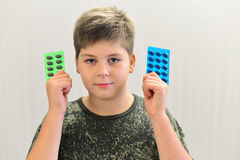 Boy in camouflage shirt holding a drugs Stock Photos