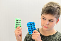 Boy in camouflage shirt holding a drugs Royalty Free Stock Image