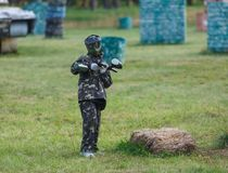 Boy in camouflage suit stands on the paintball field with his paintball gun up and looks straight ahead. team work, sport royalty free stock image
