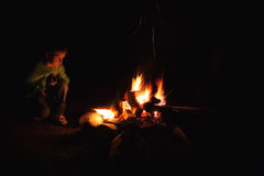 Boy camp fire. A young boy staring into a camp fire at night Stock Photo
