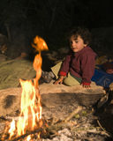 Boy at campfire stock photos