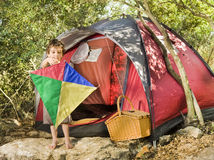 Boy camping. Camping boy holdig a kite in front of his tent and picnic basket Stock Photo