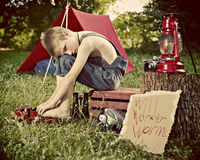 Boy camping in countryside. Young boy camping in countryside with lantern and tent in background Stock Photography