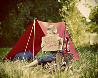 Boy camping in countryside. Young boy camping in countryside with tent and sign, fishing road in foreground, summer, scene Royalty Free Stock Image