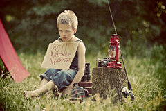 Boy camping in countryside. Young boy camping in countryside next to lantern and fishing rod Stock Photos