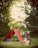Boy camping in countryside. Young boy camping in countryside with tent, looking through binoculars Royalty Free Stock Images