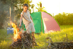 Boy on a camping trip  baking sausage Stock Images