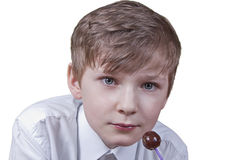 Boy with candy. Boy dressed in white shirt with brown candy, on white background Stock Photos