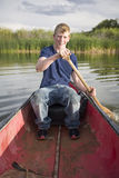 Boy in Canoe. A boy in a red canoe on a pond using a paddle to move in the water Stock Photography