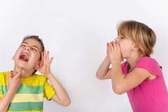 Boy cant hear. Deaf child - Boy cupping his hand behind ear because he cant hear the girl who is shouting in vain royalty free stock photo