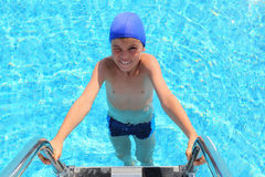 Boy in cap and melting entering in water in pool Stock Photos