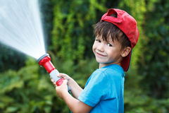 Boy in cap pours water outdoor Royalty Free Stock Photo