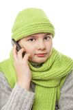 Boy with cap and scarf talking on mobile phone Royalty Free Stock Photos