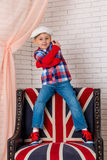 Boy in cap sits on chair with a British flag Stock Images