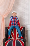 Boy in cap sits on chair with a British flag Stock Photography