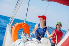 Boy captain with his sister on board of sailing yacht on summer cruise. Travel adventure, yachting with child on family. Vacation. Kid clothing in sailor style royalty free stock photos