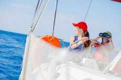 Boy captain with his sister on board of sailing yacht on summer cruise. Travel adventure, yachting with child on family. Vacation. Kid clothing in sailor style stock image