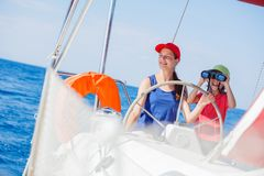 Boy captain with his sister on board of sailing yacht on summer cruise. Travel adventure, yachting with child on family Stock Photo