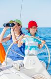 Boy captain with his sister on board of sailing yacht on summer cruise. Travel adventure, yachting with child on family. Vacation. Kid clothing in sailor style Royalty Free Stock Photo