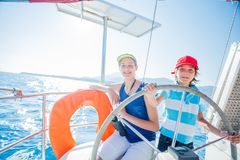 Boy captain with his sister on board of sailing yacht on summer cruise. Travel adventure, yachting with child on family. Vacation. Kid clothing in sailor style Stock Photography