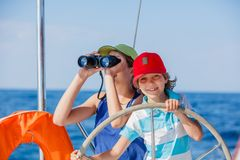 Boy captain with his sister on board of sailing yacht on summer cruise. Travel adventure, yachting with child on family. Vacation. Kid clothing in sailor style Stock Images