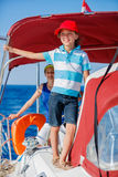 Boy captain with his sister on board of sailing yacht on summer cruise. Travel adventure, yachting with child on family Royalty Free Stock Photography