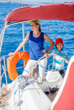 Boy captain with his sister on board of sailing yacht on summer cruise. Travel adventure, yachting with child on family Stock Image