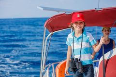 Boy captain with his sister on board of sailing yacht on summer cruise. Travel adventure, yachting with child on family Stock Photos