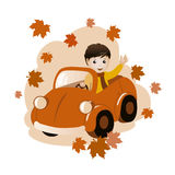 Boy in a car: fall composition. Cute little boy in an orange car and waving his hand  in a greeting or farewell. Dark-haired Caucasian boy is dressed in a yellow Royalty Free Stock Image