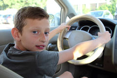 Boy in car holds the steering wheel.  Royalty Free Stock Photos