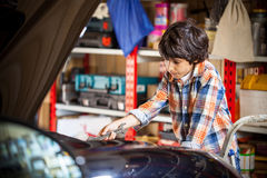 Boy car mechanic. With a wrench near a car in a car workshop on the background of shelves with accessories Royalty Free Stock Image