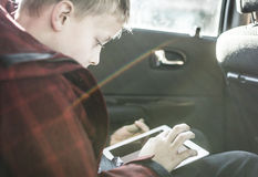 Boy in car playing on tablet pc Royalty Free Stock Photo