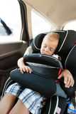 Boy and car seat safety. Stock Image