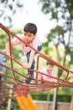 A boy Carefully climb up the rope bridge stock photos