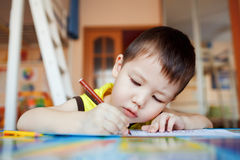 The boy carefully and intently draws in a special. Notebook for drawing, education at home, pre-school training, the development of creative abilities of royalty free stock photo