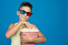 The boy carefully watches a movie in 3D glasses, with a bucket of popcorn, the concept of cinema and entertainment, picks up royalty free stock photo