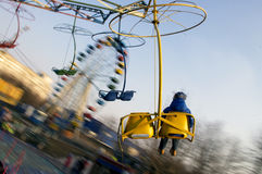 Boy on the carousel in the city park. Stock Photos