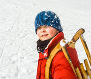 Boy carries his sledge up the hill Stock Photo