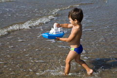 Boy carries a toy-ship Royalty Free Stock Images