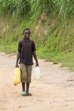 Boy carring water Royalty Free Stock Image