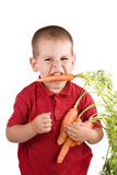 Boy and carrot. Boy eating fresh carrot isolated on white background Stock Image