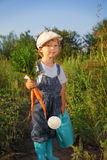 Boy with a carrot and a watering can Royalty Free Stock Images
