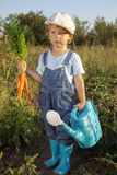 Boy with a carrot and a watering can Stock Photos